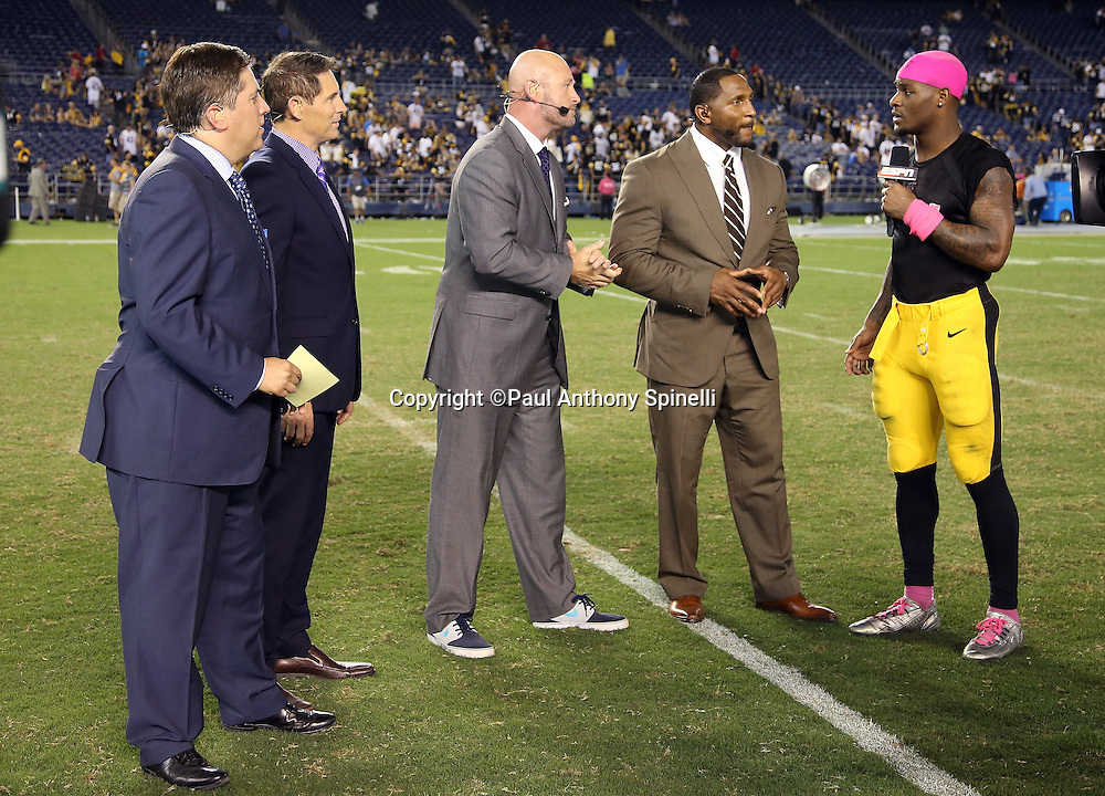 The ESPN postgame television sports analysts, including (L-R starting with second from left) Steve Young, Trent Dilfer, and Ray Lewis, interview Pittsburgh Steelers running back Le'Veon Bell (26) after Bell scores the winning touchdown after the 2015 NFL week 5 regular season football game against the San Diego Chargers on Monday, Oct. 12, 2015 in San Diego. The Steelers won the game 24-20. (©Paul Anthony Spinelli)