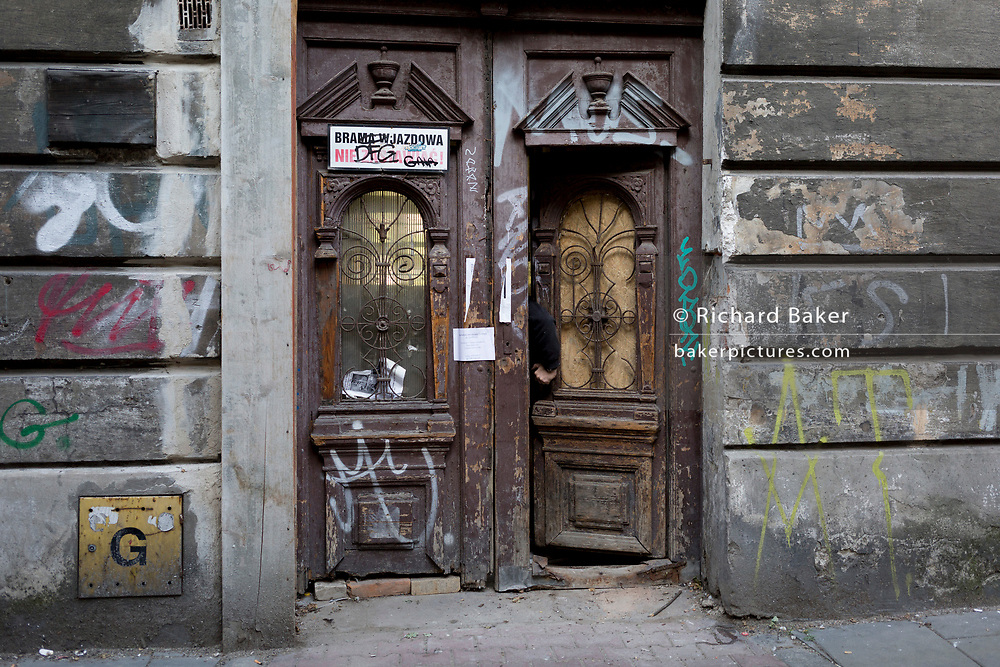 A hand in an open doorway of a property in the heart of the Jewish Kazimierz district of Krakow - the location of Nazi Holocaust evacuations during WW2 and where Steven Spielberg filmed scenes for his film 'Schindler's List', on 23rd September 2019, in Krakow, Malopolska, Poland. The Jewish community were systematically removed from Kazimierz and taken to what became the Krakow Ghetto across the Vistula river in the Podgorze district where Oskar Schindler's factory was located and where he went on to save 1,100 Jews from concentration camps all over Poland and Germany. Before the war, 64,000 Jews lived in Krakow but after liberation, only 3-4,000 survived.
