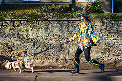 © Licensed to London News Pictures. 18/01/2020. Whittlesey UK. A Molly dancer runs with her dog to the start of the 41st Whittlesey Straw Bear Festival that is taking place this weekend in Whittlesey. In times past when starvation bit deep the ploughmen of the area where drawn to towns like Whittlesey, They knocked on doors begging for food & disguised their shame by blackening their faces with soot. In Whittlesey it was the custom on the Tuesday following Plough Monday to dress one of the confraternity of the plough in straw and call him a Straw Bear. The bear was then taken around town to entertain the folk who on the previous day had subscribed to the rustics, a spread of beer, tobacco & beef. The bear was made to dance in front of houses & gifts of money, beer & food was expected. Photo credit: Andrew McCaren/LNP
