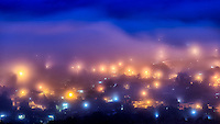 Pastel Dream: Viewed from on high of mountain - Loma de la Cruz, heavy fog wafts in layers of pastel colours over city streets, making for a dream like image in the early dawns light, Holguin Cuba.