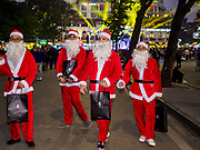23 DECEMBER 2017 - HANOI, VIETNAM: Vietnamese men dressed as Santa Claus walk through a holiday street fair in the old quarter of Hanoi. The commercial and gift giving aspect of Christmas is widely celebrated in Vietnam and Vietnam's 5+ million Catholics celebrate the religious aspects of Christmas.     PHOTO BY JACK KURTZ