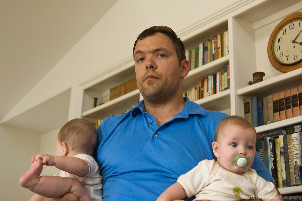 A father holds his six-month-old twin boys