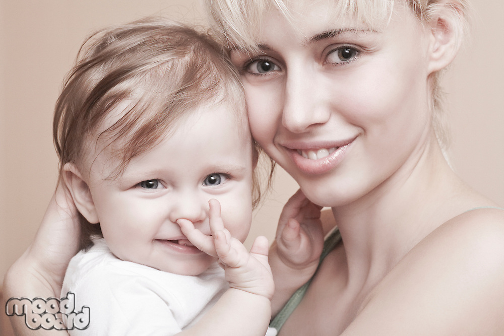 Blonde mother holds baby with hand in mouth
