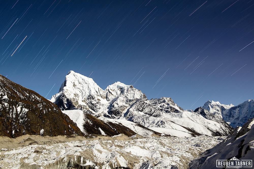 Stars above the peaks of Cholatse (6335m) and Taboche Peak (6367m) across the Ngozumba Glacier, Gokyo, Nepal.