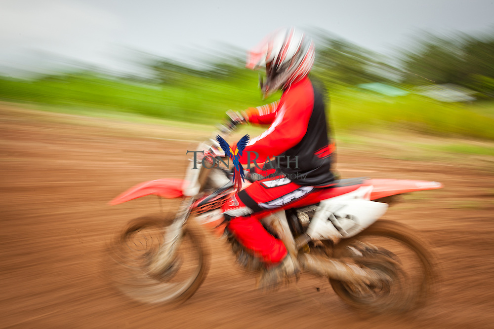 Panning shot of a motorcycle biker during motocross competition on outdoor muddy track in Belmopan, Belize.