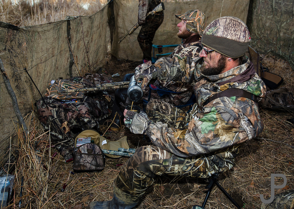 Dave Prather pours a cup of coffee while hunting in a duck blind on a private watershed lake in Shamrock, Oklahoma