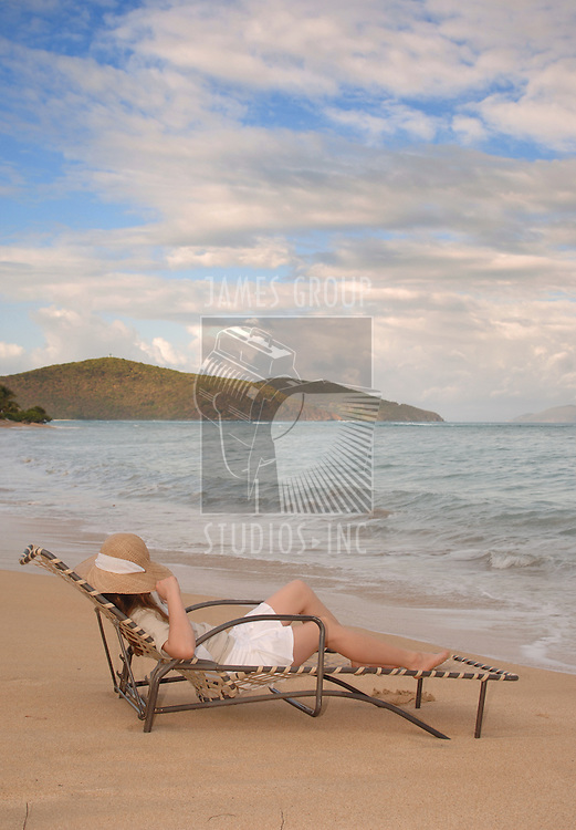 Young woman relaxing on a lounge chair near the water's edge