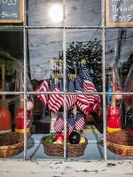 Basket of American flags in a grocery store window.