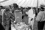 An MC wearing a shell suit raps to the crowd in front of DJ's and other local MC's at a hiphop battle, Moss Side Carnival, Alexandra Park, Manchester, 1989