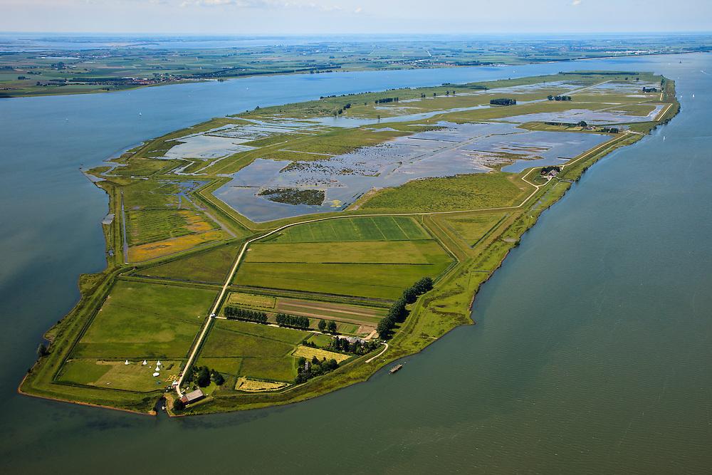 """Nederland, Zuid-Holland, Tiengemeten, 12-06-2009; eiland in het Haringvliet, overzicht naar het Westen..Oorspronkelijk gebruikt voor de akkerbouw maar inmiddels 'teruggegeven aan de natuur', de dijken zijn deels doorgestoken, de laatste boer is in 2006 vertrokken. Huidig gebruik onder andere zorgboerderij en kan er gekampeerd worden, camping met wigwams in de voorgrond. . De 'nieuwe natuur' vormt onderdeel van de Ecologische Hoofdstructuur. Oorspronkelijk was het eilandje eigendom van AMEV (Fortis Investments) - binnen de dijken, de buitendijkse slikken waren van de Vereniging Natuurmonumenten..The island Tiengemeten in the Haringvliet, originally owned - within the dikes - by AMEV (Fortis Investments), and Natuurmonumenten (Society for conservation of nature). The island was used for agriculture but has now """"been given back to nature"""", large parts have been flooded and the isle is part of the National Ecological Network. The last farmer left in 2006. Current use, among other, care farms and camping..Swart collectie, luchtfoto (25 procent toeslag); Swart Collection, aerial photo (additional fee required).foto Siebe Swart / photo Siebe Swart"""
