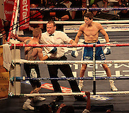 Picture by Richard Gould/Focus Images Ltd +44 7855 403186<br /> 13/07/2013<br /> The ref steps in between Luke Campbell (blue shorts) as  Andy Harris takes a pounding pictured during their Lightweight contest at Craven Park, Hull.