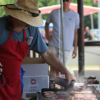George Ellis mans the grill Saturday at the 8th annual Fourth of July celebration in Guntown