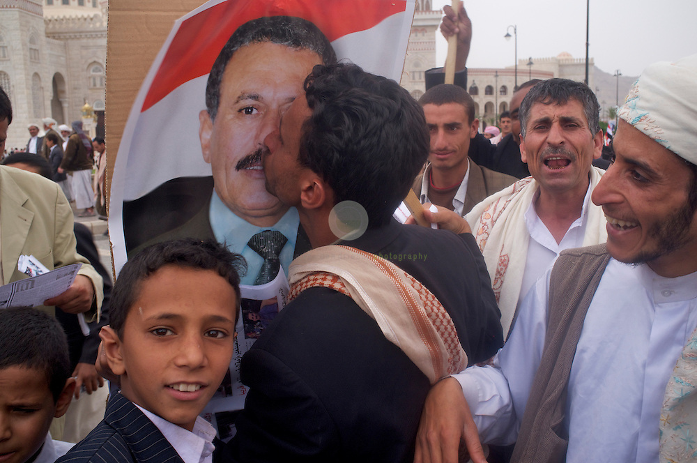 Turmoil in Yemen: ASIA, YEMEN, SANA, 24.06.2011: After the Friday prayers pro-government activists are gathering near the Grand Mosque in Sana. A man supporting President Ali Abdullah Saleh is kissing a portrait of the president.