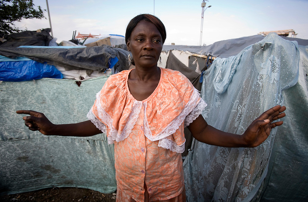 Mambo Lucienne Jean walking in next to her tent in the camp that was attack by Christian when she have a Voodoo ceremony..Faraday February  26/2010..Keeping with a long tradition of Christian missionary work in Haiti, the January 2010 earthquake brought huge numbers of Christian organizations to the country to help the devastated population with food, shelter and spiritual guidance. But the earthquake has had another, less obvious impact. Haiti has a large traditional Voodoo population. Some evangelical Christian groups not only dismiss the Voodoo religion as a Satanic cult, but in fact blame practitioners for the earthquake, saying it was God's punishment. Voodoo spiritual leaders say this belief has led to disparate treatment of earthquake victims by Christian aid groups, with Christian converts getting better tents and food, and Voodoo congregations left unattended. The tension has erupted into violent clashes and attacks on Voodoo temples in Carrefour and Cité Soleil. Voodoo leaders say missionaries are using the promise of food and medical supplies to lure people to religious meetings to convert them and complain international aid is only going to Christian groups.