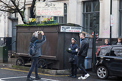London, UK. 20 December, 2019. Dave Conway, the final customer, takes a photograph of Syd's Coffee Stall, which has been run by three generations of the same family on the corner of Shoreditch High Street and Calvert Avenue since 1919, shortly before it closed for business. The mahogany coffee stall, part of east London's history, will go on display in the new Museum of London in Smithfield in 2024.