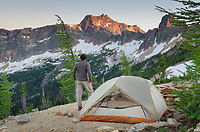 Adult male standing next to backpacking tent and gazing at view of Cutthroat Peak on ridge above Cutthroat Pass, near Pacific Crest trail. North Cascades Washington