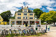 View of the Windermere Hotel from just off of Main Street, with tourists, Mackinac Island, Michigan, USA.