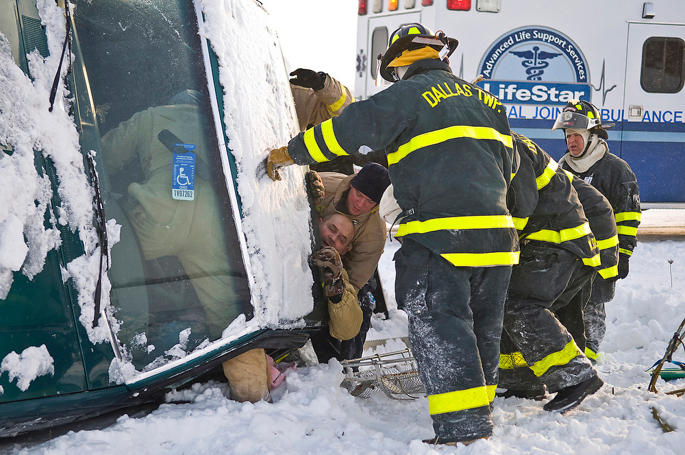 Tim Weisenauer an EMT with LifeStar in Bucyrus, Ohio along with members of the Dallas Township and Bucyrus Township Fire Departments help the driver of a truck that rolled onto its side along Crawford-Marion County Line Road approximately 1.25 miles west of State Route 98 Thursday, January 15, 2009. Fire fighters who arrived on the scene around 3:40 pm took approximately 20 mintues to remove the uninjured driver from the truck by removing the rear window and cutting away a portion of the seat.