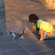 Girl playing with kitten in the piazza of the Umbrian hilltown of Montone Italy
