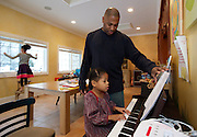 Shaun Alexander looks at music while his daughter Eden, 6, plays piano as daughter Heaven, 10, looks outside, in their home in Great Falls, VA, January 21, 2014.