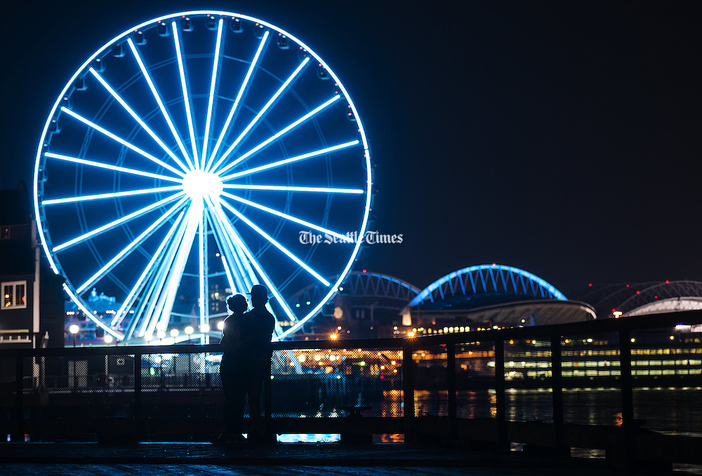 A couple enjoys a mild night on Pier 62 and 63 in Seattle as the Great Wheel and CenturyLink Field glow turquoise to raise awareness of lung disease as the American Lung Association of the Mountain Pacific kicks off National Women's Lung Health Week with a &quot;Turquoise Takeover.&quot; <br />