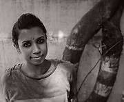 """This is a portrait from my project 'The significant other'  – as the name suggests, I do portraits of people with their significant other – friend, spouse, lover, parent or an object.  Dancer and Yoga teacher Ramya Nair was the first one to pose.  She chose a frangipani tree and its flower as her significant other.  The reason for it, in her own words  """"It reminds me of Nrityagram, whre I studied. And in a city where everyone looks alike with same hair style and same attire, the flower makes me feel different, and makes me look different. The tree is full of flowers all the time, and since it's in the middle of a chaos, nobody notices it. People walk on the fallen flowers and when they see it on my head , they actually ask me where did I get it from? !!!"""""""