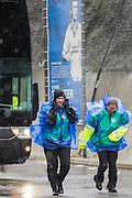 Football supporters arriving at American Express Community Stadium in the wind and rain unaware of the Norwich City FC coach behind them ahead of the Premier League match between Brighton and Hove Albion and Norwich City at the American Express Community Stadium, Brighton and Hove, England on 2 November 2019.
