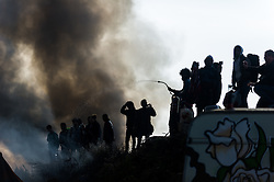 October 26, 2016 - Calais, France - Migrants try to extinguish a burning cafe in the Calais Jungle, on October 26, 2016. Huge fires destroyed a mayor part of the refugee camp today. (Credit Image: © Markus Heine/NurPhoto via ZUMA Press)