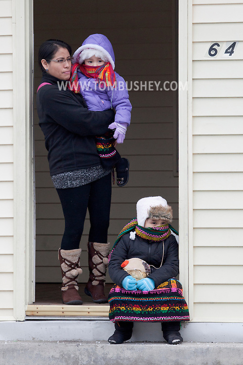 Middletown, New York - A woman and two children watch from a doorway as members of St. Joseph's Church march through the city during the festival of Nuestra Senora de Guadalupe on Sunday, Dec. 9, 2012.