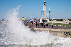 © Licensed to London News Pictures. 05/10/2016. Portsmouth, Hampshire, UK.  People out enjoying a brisk walk in the windy weather as waves crash against the seafront in Southsea this afternoon, 5th October 2016. Today is another dry and sunny, but very windy autumn day on the south coast of England. Photo credit: Rob Arnold/LNP