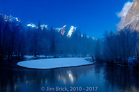 Early morning clear blue sky, the sunrise just touching the peaks around Yosemite Valley's rim, and the morning mist lifting off of the Merced river.