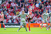 Andy Cannon (#14) of Portsmouth FC shields the ball from Grant Leadbitter (#23) of Sunderland AFC during the EFL Sky Bet League 1 match between Sunderland and Portsmouth at the Stadium Of Light, Sunderland, England on 17 August 2019.