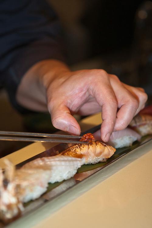 Chef Noriaki Yasutake decorates a piece of sushi with roe.