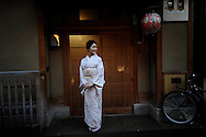 Maiko in front of her Geisha house in the Gion district of Kyoto, Japan.