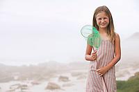 Girl (7-9) holding fishing net standing on beach portrait