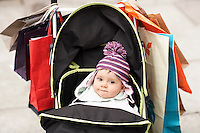 Baby sitting in stroller hung with shopping bags outdoors