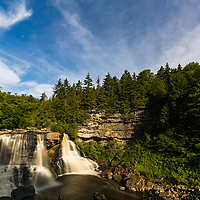 Blackwater Falls illuminated by full moon light, with Big and Little Dippers in sky above.
