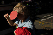 A young woman shields her eyes from afternoon sunlight with a table tennis (pingpong) bat.