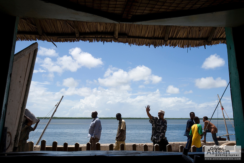 Men walking by on seafront seen through window in Lamu, Kenya.