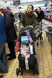 © Licensed to London News Pictures. 19/03/2020. London, UK. Customers queue up with their items in a Lidl supermarket as panic buying sets in due the threat of Coronavirus spreading. Photo credit: London News Pictures