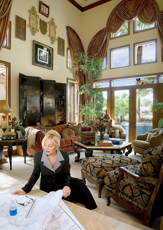 beautiful blond woman sitting in living room looking at blueprints on a sunny day.