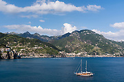 A yacht rest at-anchor in the blue sea just off the Amalfi Coast, near Minori, Italy