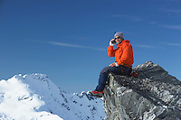 Mountain climber using walkie-talkie on mountain peak