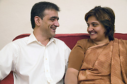 Couple sitting on the sofa at home; smiling,