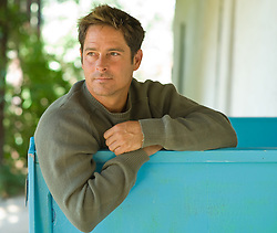 Handsome Man in a green sweater  on a blue bench