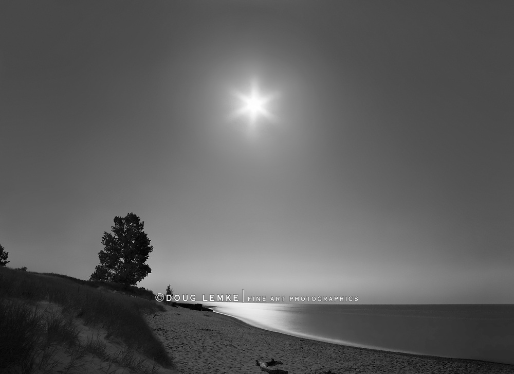Night meets day along the moonlit Lake Michigan shore at the Point Betsie Lighthouse just before sunrise, Michigan's Lower Peninsula, USA