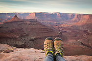 Hiking boots at the edge of a canyon lend a point of view experience at Dead Horse Point State Park, near Moab, Utah.
