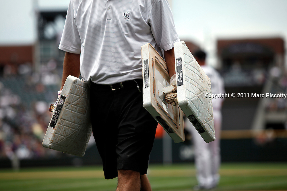 SHOT 8/24/11 3:14:49 PM - A Colorado Rockies grounds crew member carries some extra bases after changing them out between innings during a game against the Houston Astros during their regular season MLB game at Coors Field in Denver, Co. The Rockies won the game 7-6 in 10 innings. (Photo by Marc Piscotty / © 2011)