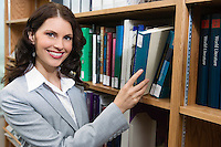 Portrait of woman reaching for book from bookshelf