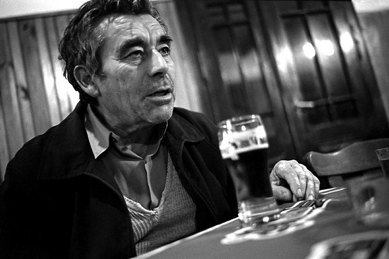 .A man in a bar disscussing politics and unemployment. High unemployment and alcohol are a major feature of village life. From Neighborhoods series.**Neighborhoods